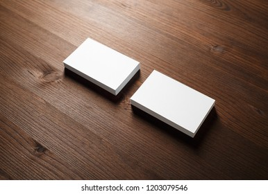 Mockup of blank business cards on wooden background.