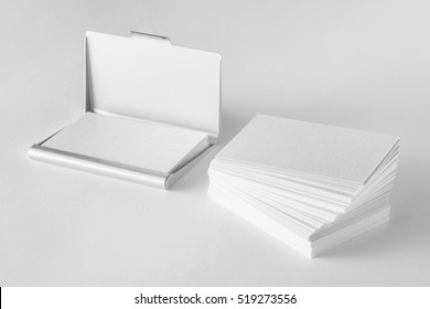 Mockup of blank business cards stack and cardholder at white textured background.