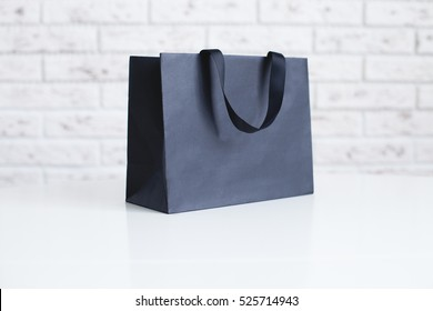 Mock-up of blank craft package, mockup of black paper shopping bag with handles on the white background