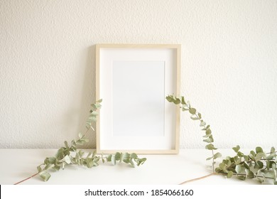Mockup of a blank frame in portrait layout with dried out leaf deco