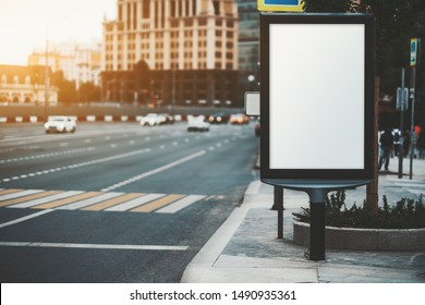 Mockup of a blank information poster in urban settings near the crosswalk; an empty vertical street banner template on the sidewalk; a narrow outdoor billboard placeholder mock-up near a big road