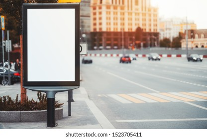 Mockup of a blank narrow info poster in urban settings near a crosswalk; an empty vertical street banner template on a sidewalk; an outdoor billboard placeholder mock-up near a road with rare cars