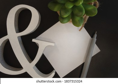 Mockup blank note with pen, wood ampersand & succulent on black background top view