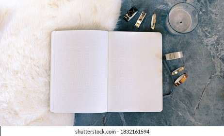 mockup  of blank notebook on cosy lamb fur on grey textured stone background