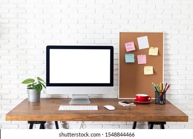 Computadora de pantalla en blanco en un escritorio de madera. pantalla blanca vacía de escritorio, con espacio de trabajo y suministros de oficina en la mesa