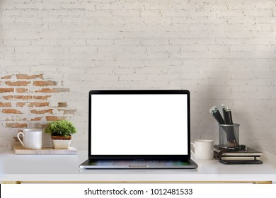 Mockup blank screen laptop on desk. Workspace with laptop and office supplies.