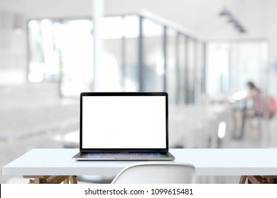 Mockup blank screen laptop on wood table in co-working space.