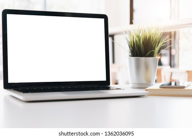 Mockup blank screen laptop on workspace table top in living room background