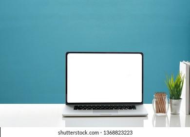 Stecken Sie einen leeren Bildschirm-Laptop mit Bleistift, Bücher und Hauspflanze auf weißem Tisch und blauer Zementwand ein.