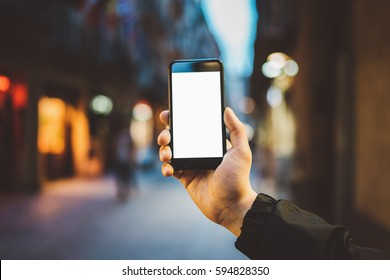 Mockup of blank screen of smartphone, male hand holding modern black cellphone with template screen with area for your logo or design, evening city street in the background