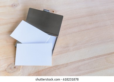 Mockup of blank white business cards on a wood table. Business cards typically include giver's name, company or business affiliation with logo and contact information i.e street address, phone number.