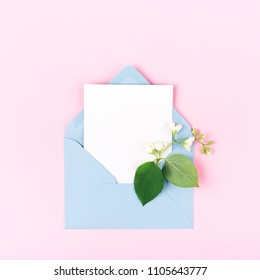 Mockup with blue envelope and jasmine flower on pink background. Minimal styled flat lay in pastel colors.