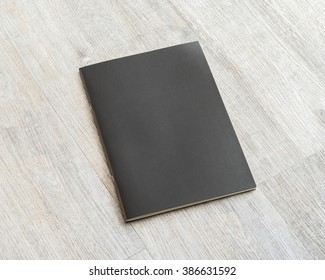 Mockup book blank black A4 leather cover for magazine, booklet, brochure, menu, diary, business portfolio mock-up design template on wooden table background