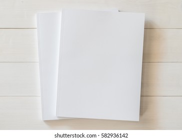 Mock-up book cover blank A4 size paperback mockup for catalog, magazine booklet, portfolio, menu design template with page front side on white surface on wood table