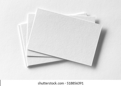 Mockup of business cards fan stack at white textured paper background.