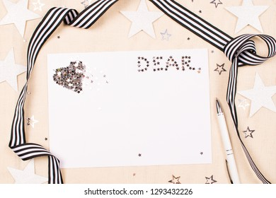 Mockup with a card and pen for writing a greeting for someone Dear on fabric background decorated with shiny star-shaped confetti and striped ribbon. Cozy women's creative world. Love message concept.