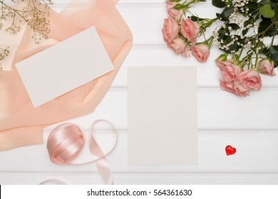 Mockup. Cards and flowers, roses, pink ribbon and cloth lying on a white table.