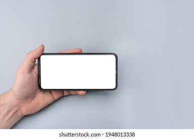 Mockup cell phone. male hand holding phone horizontally with blank white screen. Mockup phone horizontal. human left hand holding black horizontal mobile phone - Shutterstock ID 1948013338