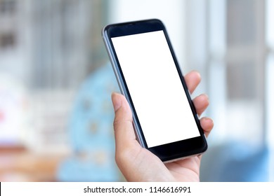mockup a cellphone in a restaurant with a blank white screen. Woman holding a black mobile