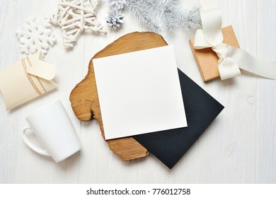 Mockup Christmas black greeting card letter in envelope and mug, flatlay on a white wooden background, with place for your text. Flat lay, top view photo mock up