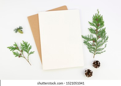 Mockup Christmas greeting card letter on craft paper envelope with fur tree branches, flatlay on a white background. Mock up with copy space for lettering text