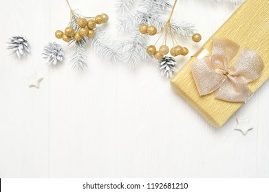 Mockup Christmas white tree, beige bow, gift box and cone. Flat lay on a white wooden background, with place for your text. Top view