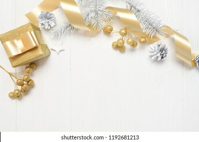 Mockup Christmas white tree, beige bow, gold gift box and cone. Flat lay on a white wooden background, with place for your text. Top view