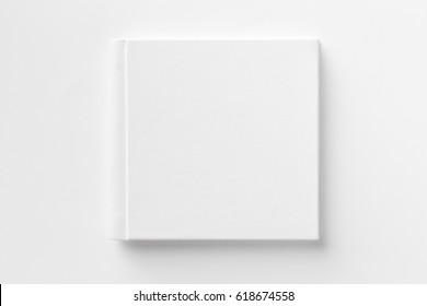 Mockup of closed blank square book at white textured paper background.