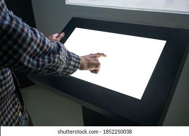 Mockup closeup image: man hand touching white empty interactive touchscreen display kiosk in dark room of technology museum. Mock up, template, scifi, education, futuristic and technology concept