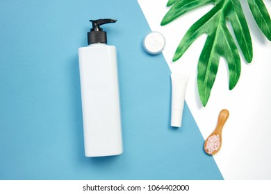 Mockup of cosmetic cream bottle, Blank label package and ingredients on a green leaves background. Concept of natural beauty products.
