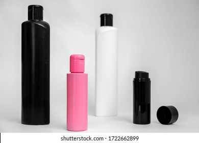 Mockup of cosmetic products isolated. Similar black and white plastic bottles, with small pink tare with no label, for designers visualization