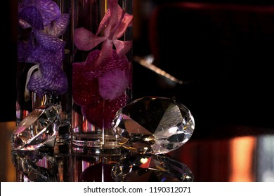 mockup daimonds put on a glass top table near by vase of orchids