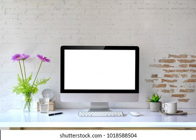 Mockup desktop Blank screen modern computer, coffee mug, house plant, bouquet and office supplies.
