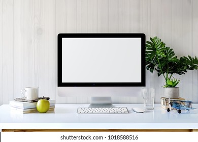 Mockup desktop Blank screen modern computer, coffee mug, house plant, vintage toy and office supplies.