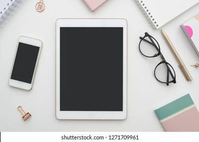 Mockup. Digital tablet with blank screen, smartphone and notepad on table. Woman office workspace. Blog concept.