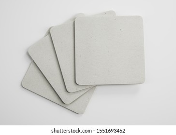 Mockup of empty blank beer drink paper cardboard coasters in studio environment on bright white background