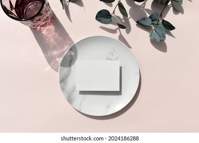 Mockup empty blank invitation card, marble plate color glass and with eucalyptus leaves on sunlit beige background. Elegant minimal tableware composition for wedding, restaurant menu or business.