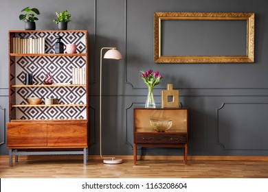 Mockup of empty gold frame above cabinet in grey retro living room interior with lamp. Real photo