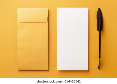 Mockup of envelope, blank white paper and vintage ink pen at golden paper background.