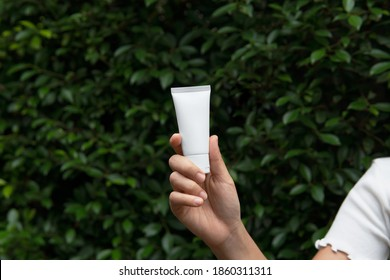 Mockup facial skincare white tube product with blank label holding by woman's hand with Ficus annulata (Banyan-Baum) green bush nature background and copy space