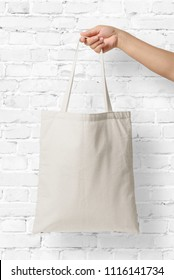 Mockup of female hand holding a blank Tote Canvas Bag on white brick wall background. High resolution.