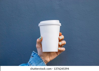 Mockup of female hand holding a Coffee paper cup isolated on dark background