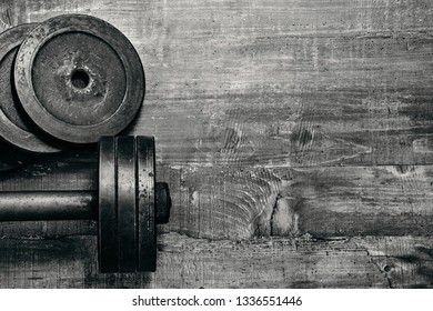 Mockup Fitness workout equipment. Dumbbell or barbell on a wooden floor surface. Flat lay black and white concept picture