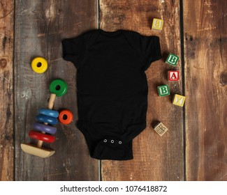 Mockup Flat Lay of black baby bodysuit shirt on rustic wood background with wooden blocks and baby toys