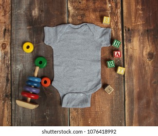Mockup Flat Lay of gray baby bodysuit shirt on rustic wood background with wooden blocks and baby toys