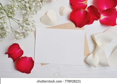 Mockup Flowers composition from gypsophila with a heart letter with red rose petals on white wooden background. Valentine's Day. Flat lay, top view with a place for your text