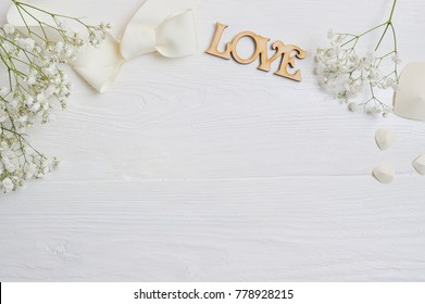 Mockup Flowers composition from a white gift gypsophila with a heart and an inscription Love on white wooden background. Valentine's Day. Flat lay, top view with a place for your text