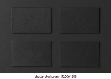 Mockup of four black business cards arranged in rows at black paper background.