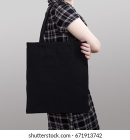 Mock-up. Girl in dress carries black cotton tote bag.