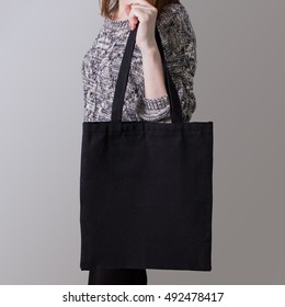 Mock-up. Girl is holding black cotton tote bag. Handmade eco shopping for girls.